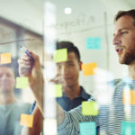 Cropped shot of coworkers using sticky notes on a glass wall during a meeting